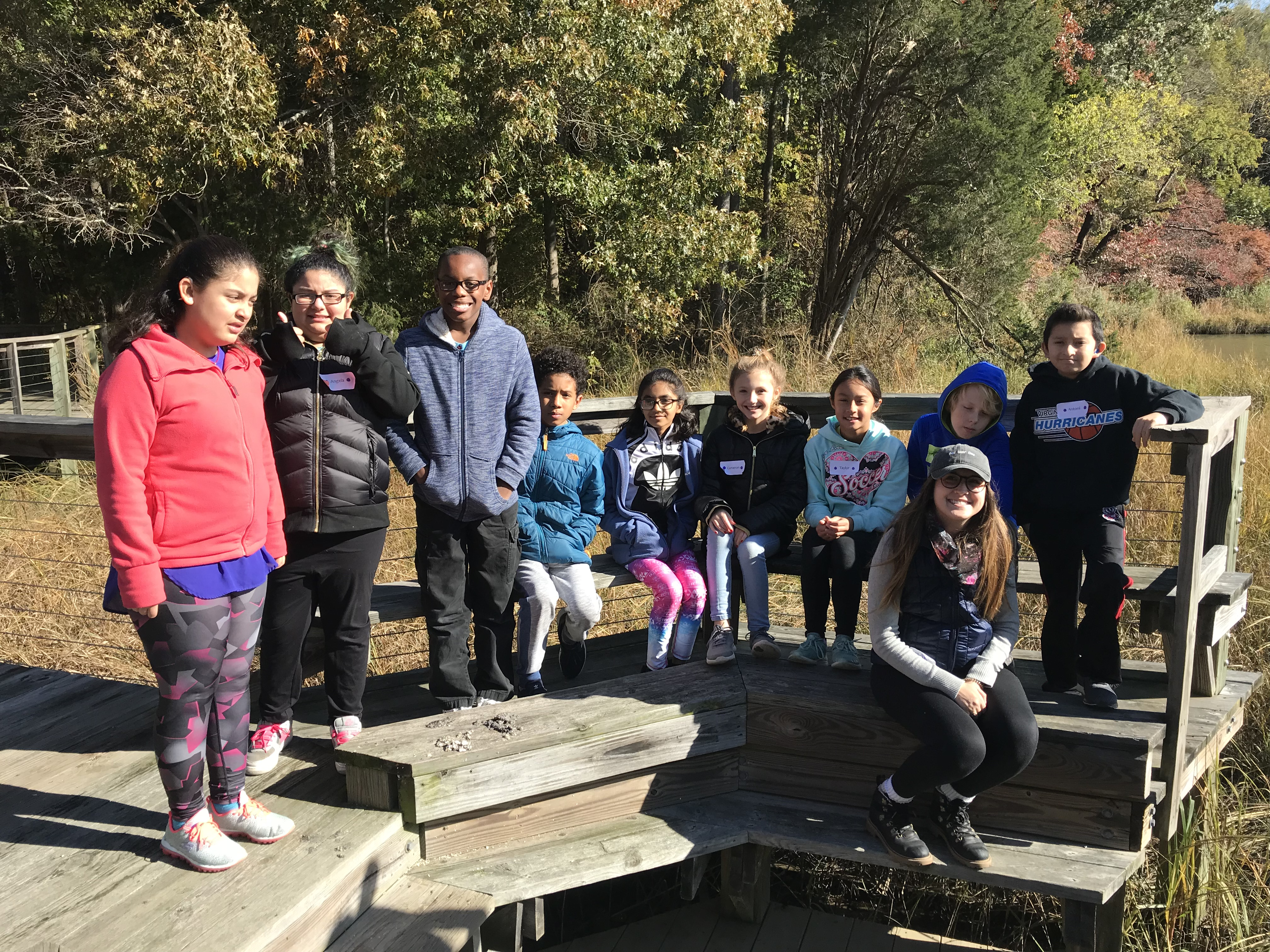 Students standing on dock of pond at the outdoor lab