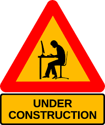 Under Construction Sign with Person on a computer in the middle
